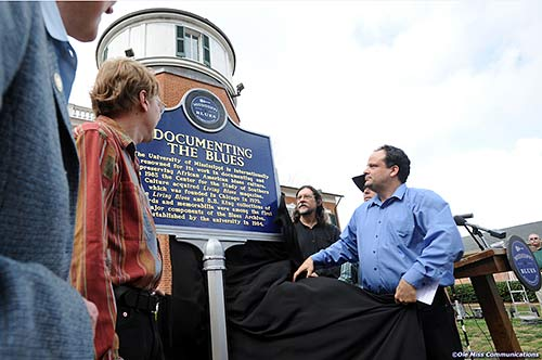 "Mark Camarigg, publications manager of Living Blues magazine, Jim O'Neal, co-founder of LB, Brett Bonner, LB editor, and Scott Barretta, Highway 61 Radio host unveil the Blues Marker honoring ""Living Blues"" magazine published at The University of Mississippi."