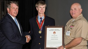 UM graduate Kerry Commander, (center), is presented with the National Defense Industrial Association Bronze Medal for achievements in Science and Technology. | Photo courtesy U.S. Navy.