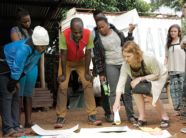 In Tanzania, Laura Johnson (right), associate professor of psychology, and Simon Mtuy (third from left), a world-class athlete and conservationist, discuss a community mapping project of Mount Kilimanjaro, the highest mountain in Africa, conducted by Tanzanian research partners and UM study abroad students. In Faces of the Mountain, a project funded by the National Geographic Conservation Trust and a UM College of Liberal Arts Senior Scholar Research Grant, Johnson and Mtuy collaborate with partners from the Jane Goodall Institute and forest villages to conduct research that brings visibility and voice to conservation initiatives in the region facing numerous ecological threats. Mtuy advised the team about forest villages, the route around the mountain, and challenges in the field.