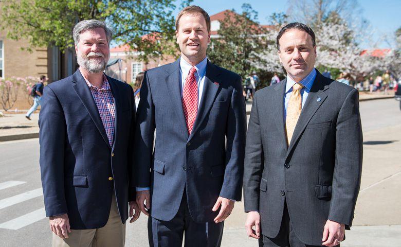 Denson Hollis (center), senior director of development for the UM College of Liberal Arts, congratulates School of Business Dean Ken Cyree (left) and Liberal Arts Dean Lee Cohen.