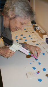 Nancy Wicker works with polyvinyl siloxane to make impressions from broken portions of bracteates.