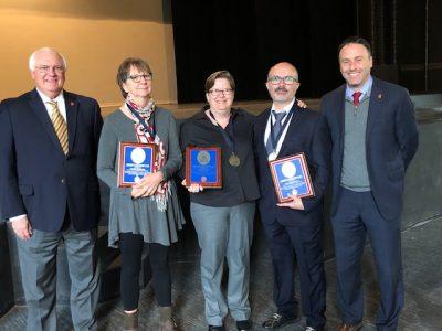 Dean Lee Cohen, far left, and Associate Dean Charles Hussey, far right, congratulate UM's 2017