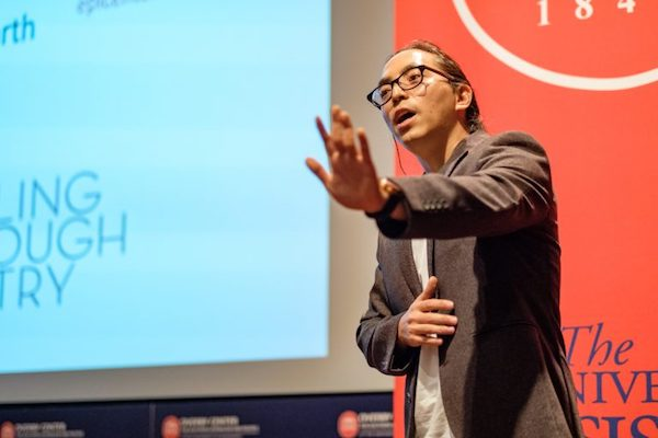 """Samyak Shertok presents his thesis, """"In the Year of the Earth: Notes from the Epicenter,"""" at the Three Minute Thesis competition at UM. Photo by Robert Jordan"""