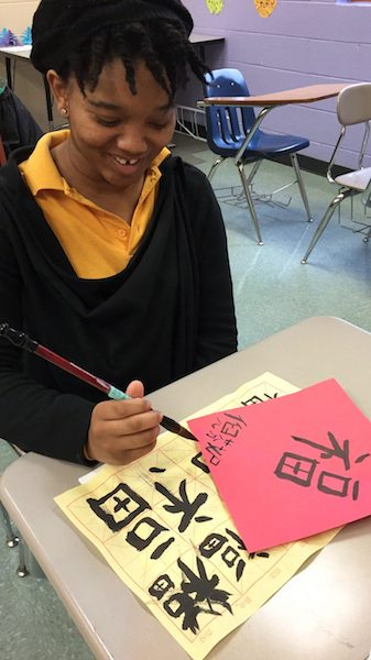 Tiffany Nichols, a student in the Chinese language program at Holly Springs High School, writes her first 'good luck' poster with the Chinese brush. UM photo by Linfei Yi