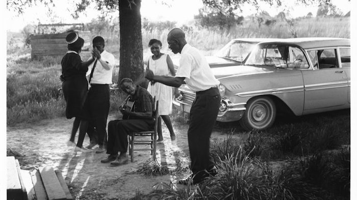 Blues musician Fred McDowell (seated) plays guitar and sings at a house party in the Southeast Emmy-nominated documentary 'Shake 'Em On Down: The Blues According to Fred McDowell.'