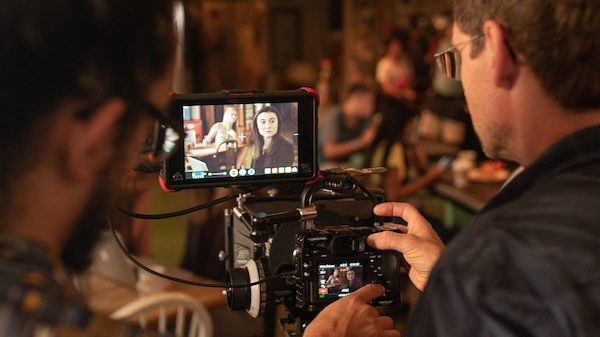 UM film production professor Harrison Witt (right) works with cinema student Sam Cox to set up a shot in Bottletree Bakery near the Oxford Square. Pictured on the screen is former Ole Miss acting student Darbianna Dinsmore, who plays special agent Grace Henderson in the short film 'MANGRY.'