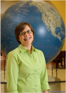 Picture of Sarah Moses in front of the globe in the lobby of Bryant Hall