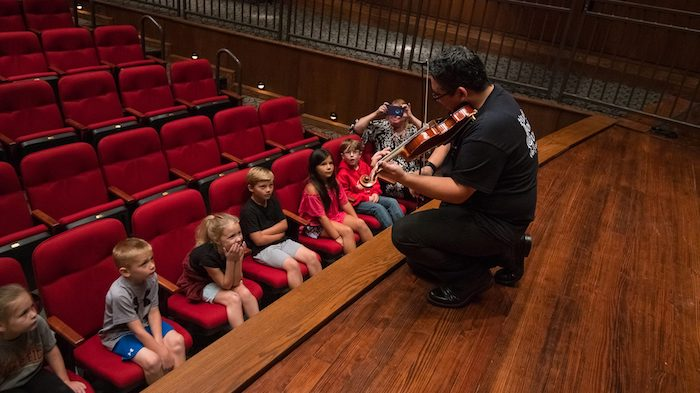 Alex Urbina (right), a UM graduate student and section leader in the LOU Symphony Orchestra, lets Oxford second-graders get a close-up view of his playing during a special presentation of 'Peter and the Wolf' at the Ford Center. Photo by Kevin Bain/