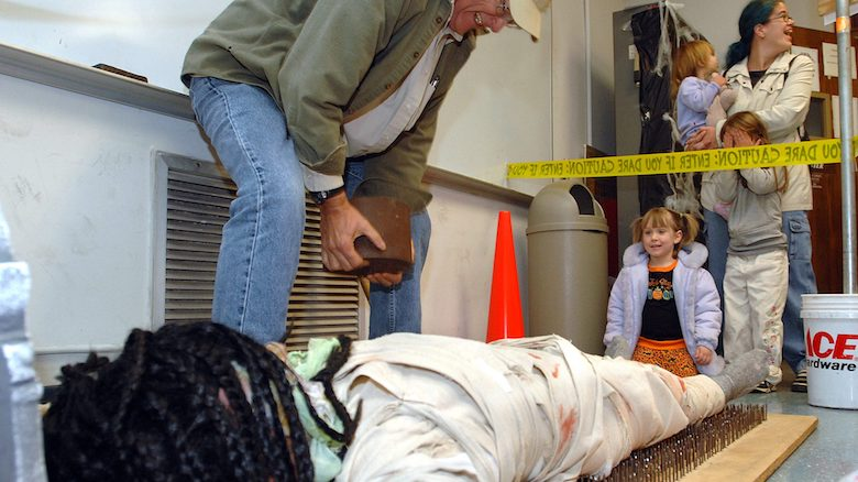 An Oxford Elementary School student lies on a bed of nails as a volunteer places a weight on her while other Spooky Physics Night participants observe. Photo by Nathan Latil