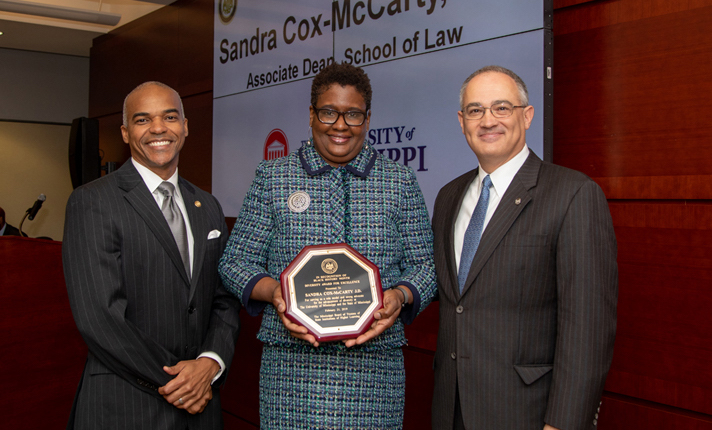 Dr. Steven Cunningham (left), chair of the IHL Diversity Committee, and UM Interim Chancellor Larry Sparks (right) congratualte Sandra Cox-McCarty on winning one of hte board's Excellence in Diversity Awards.