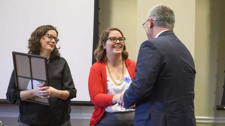 Erin Oeth (left), project manager with the UM Division of Diversity and Community Engagement, and Interim Chancellor Larry Sparks (right) congratulate Anne Cafer on winning an Algernon Sydney Sullivan Award at the 2019 Celebration of Service. Cafer, an assistant professor of sociology and coordinator for the Applied Policy and Community Research Institute, was honored for her research and her work with students. Photo by Thomas Graning