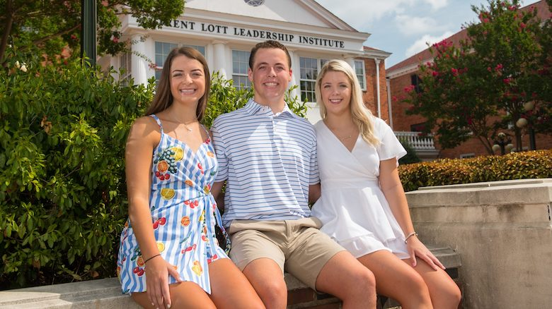 Freshman siblings (from left) Sophia, Calvin and Isabella Sanders share a moment outside the Trent Lott Leadership Institute at the University of Mississippi. The triplets, who hail from Jefferson City, Missouri, are all majoring in public policy leadership. Photo by Kevin Bain